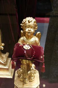 手捧装饰品的金色小男孩雕塑