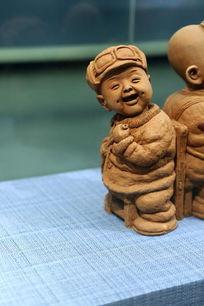 泥塑带帽子和眼镜的小男孩雕像