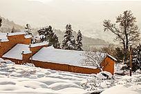 冬雪衬托着金龙山红土房