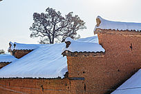 金龙山村落红土房的马头墙上厚厚的冬雪