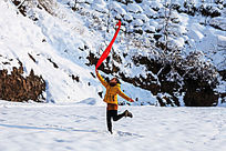 雪地里一个女孩手持红丝巾在跳跃