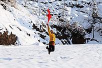雪地里一个女孩手持飘着的红丝巾在跳跃