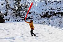 雪地里一个女孩手持迎风飘着的红丝巾