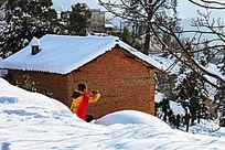 一个黄衣女孩持着手机在雪地里拍照