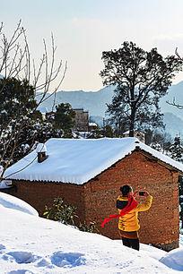 一个女孩持着手机在雪地的土房前拍照