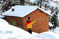 一个女孩持着手机站在雪地里拍照