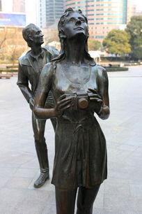 铜雕像手持相机的美女游客