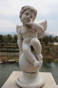 长翅膀的天使男孩抚脸石雕像