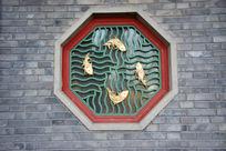 金鱼雕饰的窗户与灰墙壁