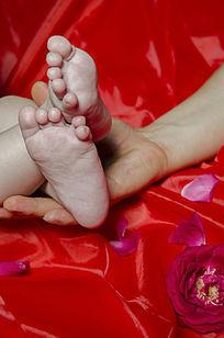 背景红色父亲握着婴儿的小脚