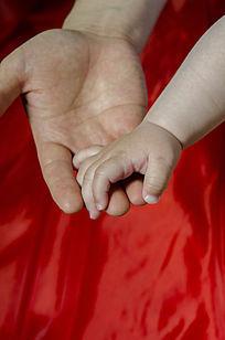 红色背景父亲托起孩子的手