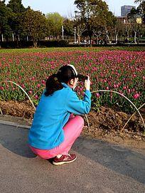 手机拍摄花卉的少女
