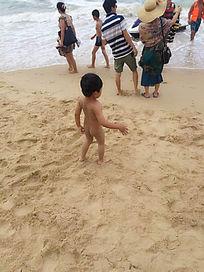 沙滩边光屁股的小孩