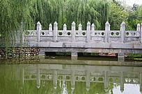 柳树林里倒影在水中的石桥