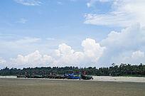 蓝天白云海滩上的成排渔船