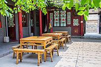 树叶下的古朴的客栈木桌椅