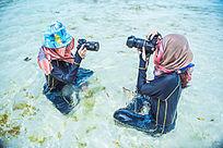 两个美女拿着相机互相拍照