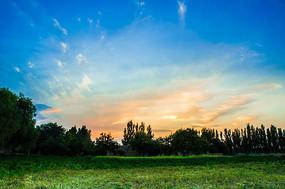 日落后夕阳下的麦田和远处的村庄