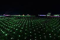 绿色灯光打扮下的田野上的彩灯