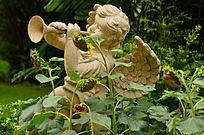 花丛中吹笛子的小孩雕像
