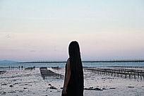 沙滩边夕阳下的少女