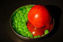红色西红柿与绿色糖果