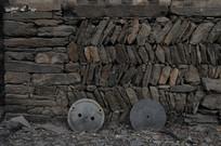 墙边废弃的石磨