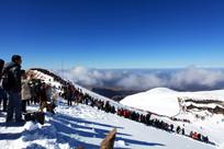 坡路积雪游客云彩长白山