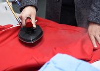 电熨斗在熨红色衣服