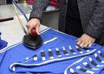熨斗熨蓝色运动服
