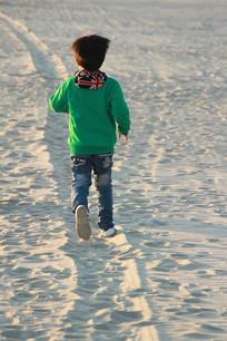 夕阳沙滩奔跑男孩儿童背影沙滩脚印