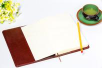 白色桌面的笔记本和茶杯