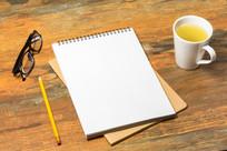 办公桌上的空白笔记本和茶杯