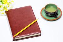 纯色背景的笔记本和茶杯