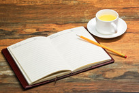 办公桌的白色茶杯和打开的笔记本