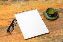 办公桌上的笔记本和绿色茶杯