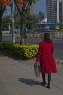 红色风衣女子行走的背影