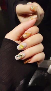 贴上钻石的女性指甲