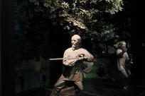 石雕练习太极剑的老人