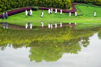 城市路缘花境企鹅雕塑和池塘倒影