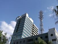 蓝天下的办公大楼与信号塔