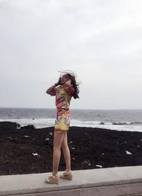 长发美女穿短旗袍站海边风吹发乱