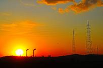 夕阳中的发电厂烟囱与山脉线架子