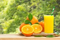 植物背景的橙汁在木桌上