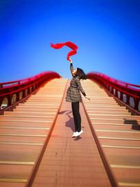 桥上舞动丝带跳跃的女孩