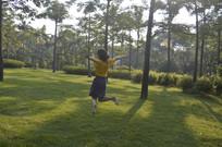 在草地上跳起来的女孩