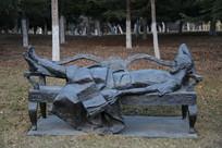 石雕躺在长椅上的老人雕像