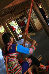 用织布机纺织的拉祜族女孩