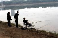 老人在湖边休闲垂钓