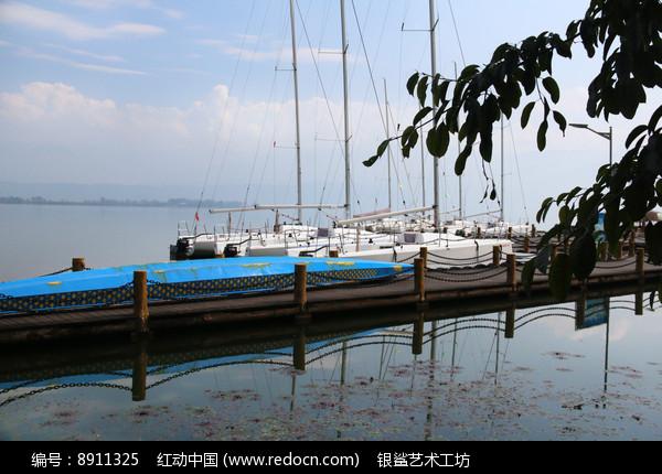 停靠在木桥边的帆船图片